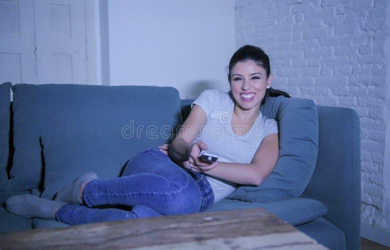 mulher latin bonita e feliz nova em seu 30s que guarda o telecontrole da tevê que aprecia em casa o programa televisivo de observ imagens de stock royalty free
