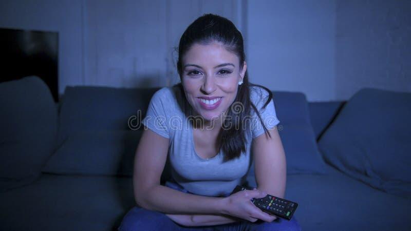 mulher latin bonita e feliz nova em seu 30s que guarda o telecontrole da tevê que aprecia em casa o programa televisivo de observ imagem de stock