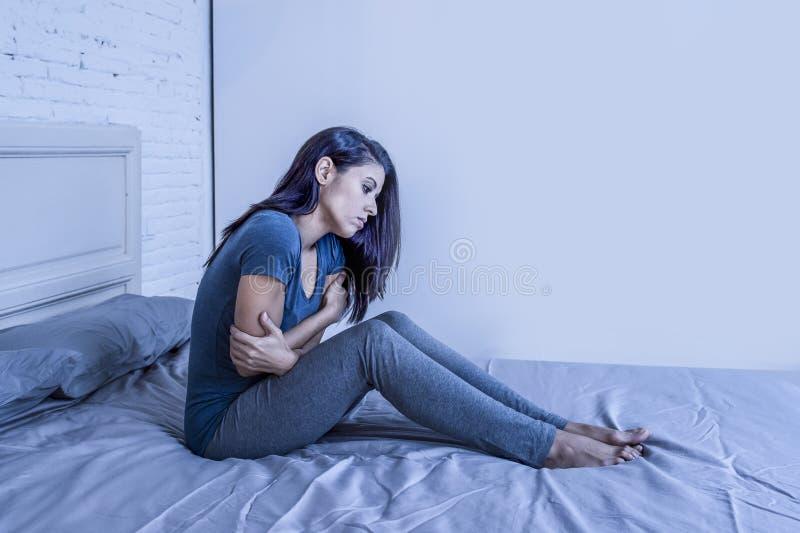 Mulher latin bonita e triste só nova em casa que sofre a dor do período ou que sente assento doente e deprimido na cama insolúvel imagens de stock royalty free