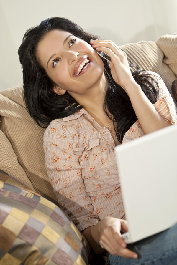 Mulher Latin bonita no telefone & no portátil de pilha   foto de stock royalty free