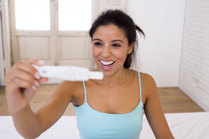 Mulher latin bonita que guarda o teste de gravidez que olha e que encontra o sorriso do resultado positivo feliz e entusiasmado imagens de stock