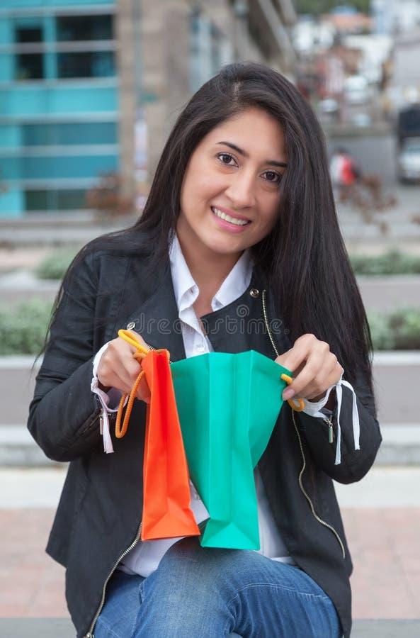Mulher latin de riso que olha seus sacos de compras fotografia de stock royalty free