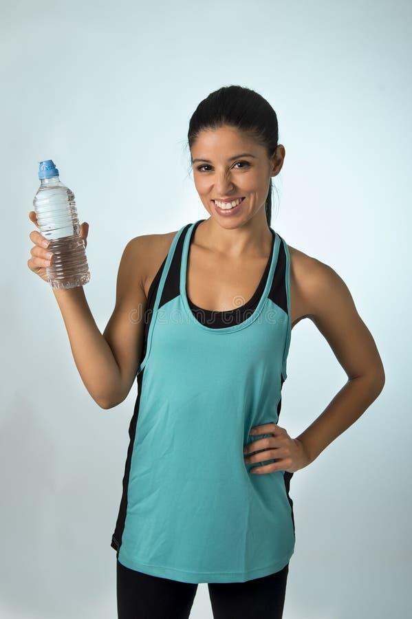 A mulher latin feliz e atrativa do esporte na aptidão veste manter o sorriso da água potável da garrafa fresco e alegre fotografia de stock