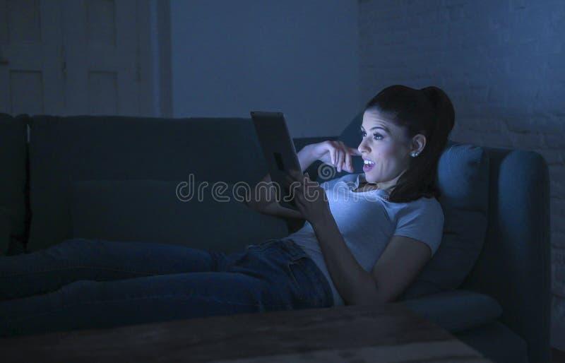 Mulher latin feliz e relaxado bonita nova 30s que encontra-se na observação digital de utilização tardio da almofada da tabuleta  imagem de stock