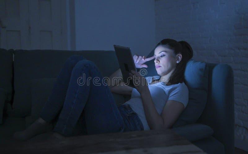 mulher latin feliz e relaxado bonita 30s que encontra-se na observação digital de utilização tardio da almofada da tabuleta do po imagens de stock