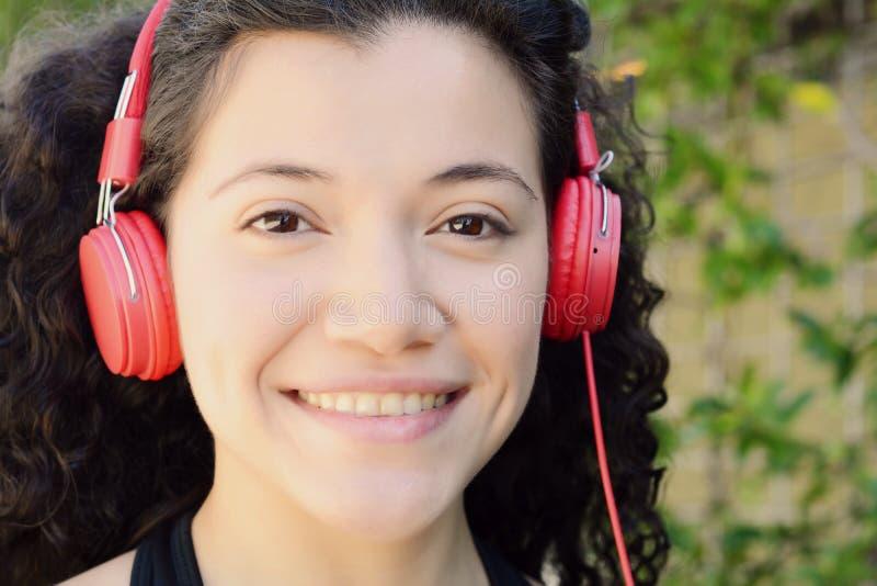 Mulher latin nova com fones de ouvido em um parque fotografia de stock royalty free