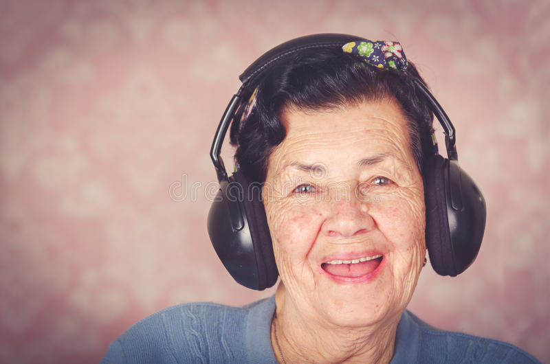 Mulher latino-americano adorável mais idosa que veste a camiseta azul, curva do teste padrão de flor na cabeça na frente do papel fotografia de stock royalty free