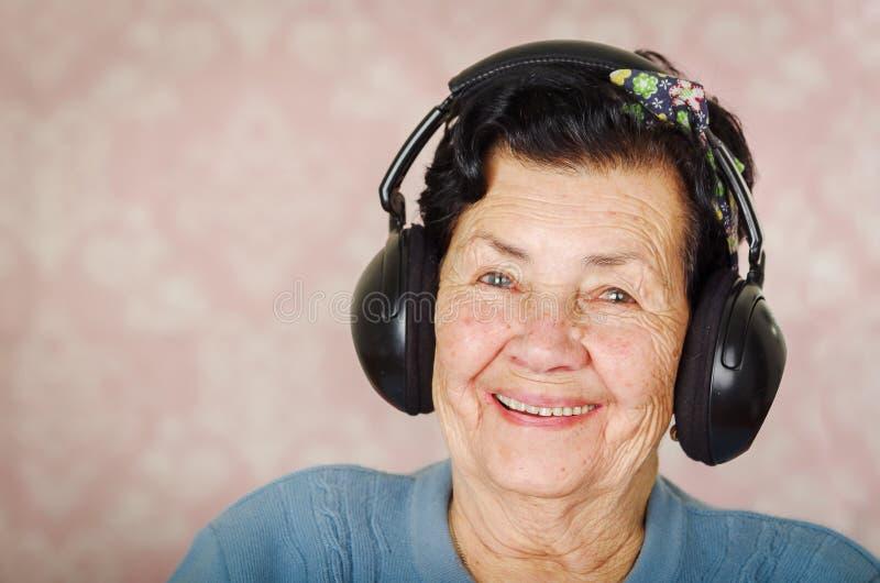 Mulher latino-americano adorável mais idosa que veste a camiseta azul, curva do teste padrão de flor na cabeça na frente do papel foto de stock royalty free