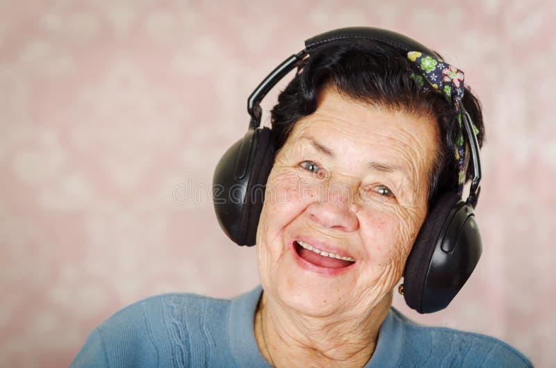 Mulher latino-americano adorável mais idosa que veste a camiseta azul, curva do teste padrão de flor na cabeça na frente do papel imagem de stock royalty free
