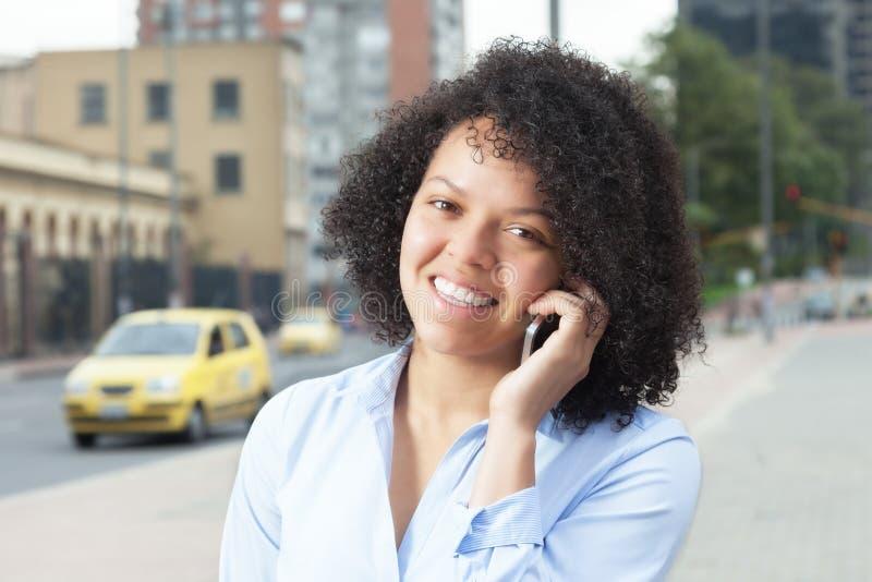 Mulher latino-americano atrativa na cidade que chama um táxi imagem de stock