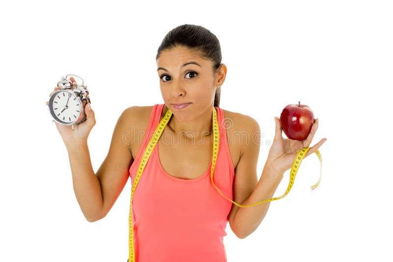 Mulher latino-americano bonita e apta que guarda a medida da fita do fruto e do taylor da maçã do despertador imagens de stock royalty free