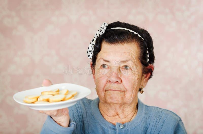 Mulher latino-americano bonito mais idosa que veste o bowtie azul da camiseta e do às bolinhas na cabeça que sustenta uma placa d imagem de stock