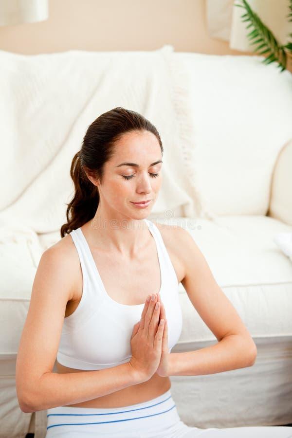Mulher latino-americano concentrada que meditating em casa imagem de stock royalty free