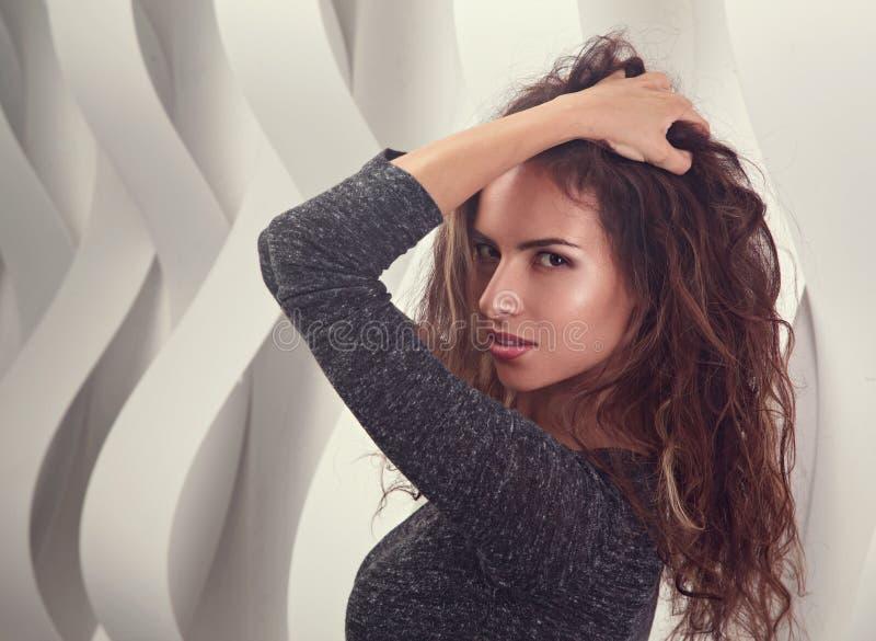Mulher latino-americano da composi??o 'sexy' que levanta no fundo preto da parede com cabelo encaracolado longo Retrato do close  imagens de stock royalty free