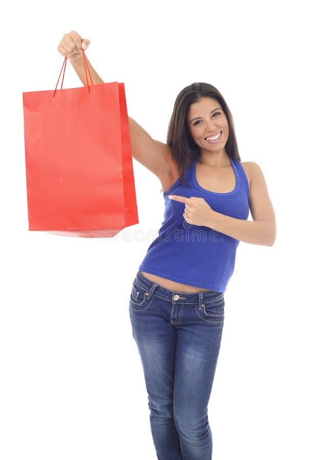 Mulher latino-americano feliz e bonita nova que mantém entusiasmado de sorriso do saco de compras vermelho isolado no branco fotografia de stock