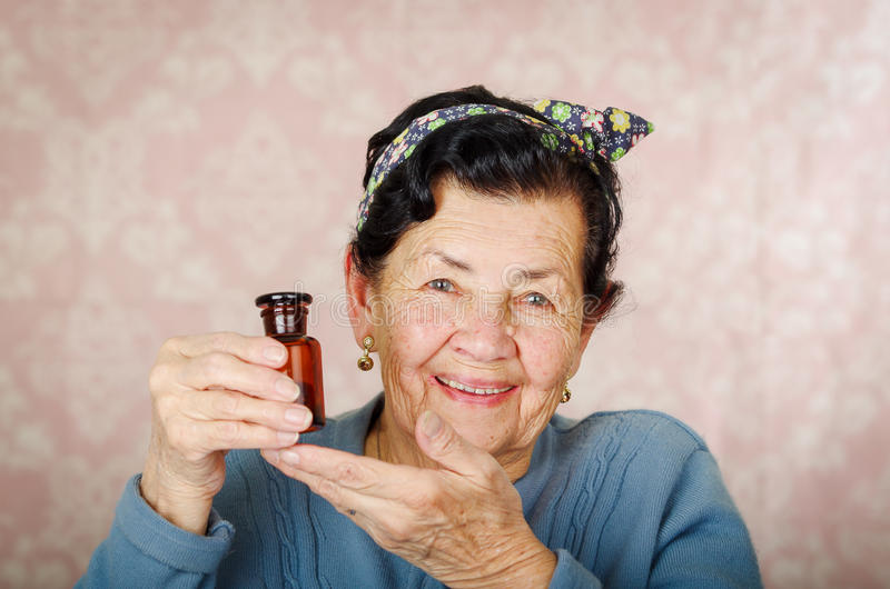 Mulher latino-americano fresca mais idosa que veste a camiseta azul, a curva do teste padrão de flor na cabeça que sustenta uma g fotos de stock royalty free