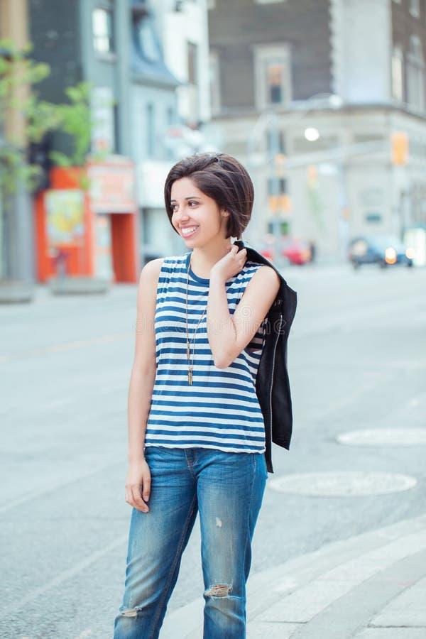 Mulher latino-americano latin nova de sorriso bonita da menina com o prumo escuro curto do cabelo preto, parte externa na rua mov fotografia de stock royalty free
