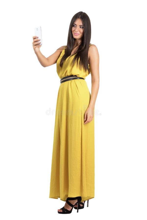 Mulher latino-americano lindo sensual no fato-macaco amarelo que toma o selfie do telefone celular com uma mão fotos de stock royalty free