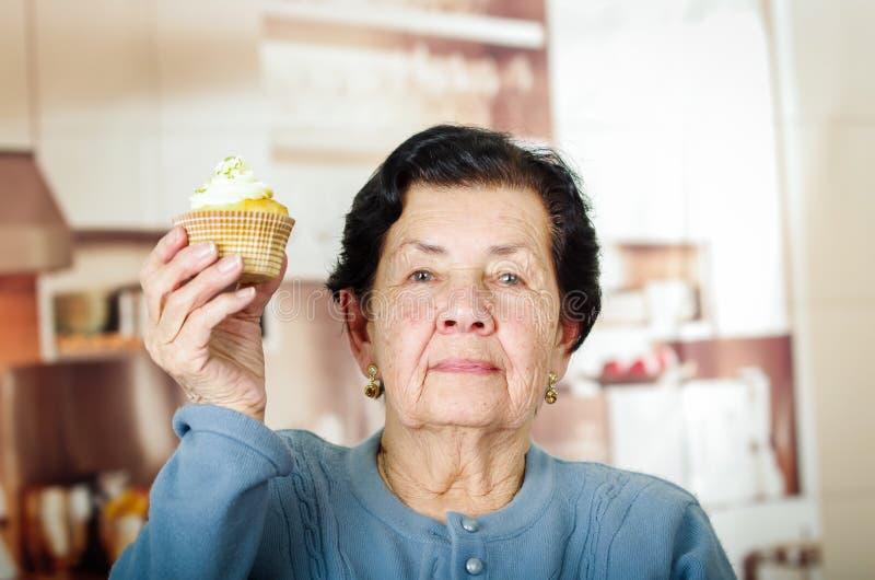 Mulher latino-americano mais idosa que veste o assento azul da camiseta fotografia de stock royalty free