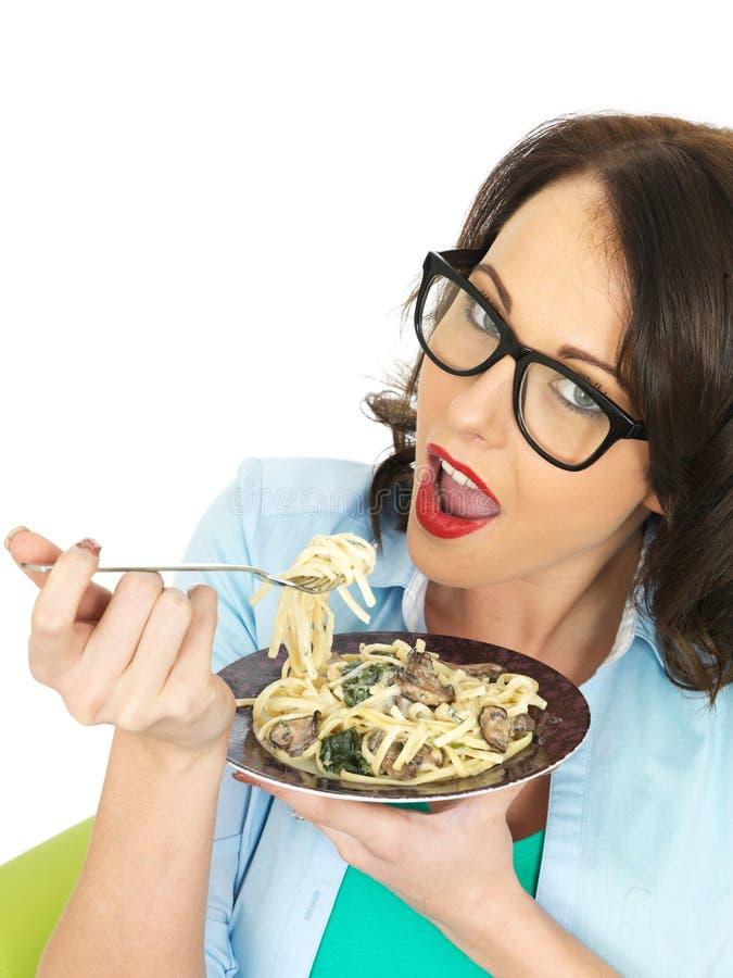 Mulher latino-americano nova feliz bonita que come uma placa do Linguine do vegetariano com espinafres e cogumelos imagem de stock royalty free