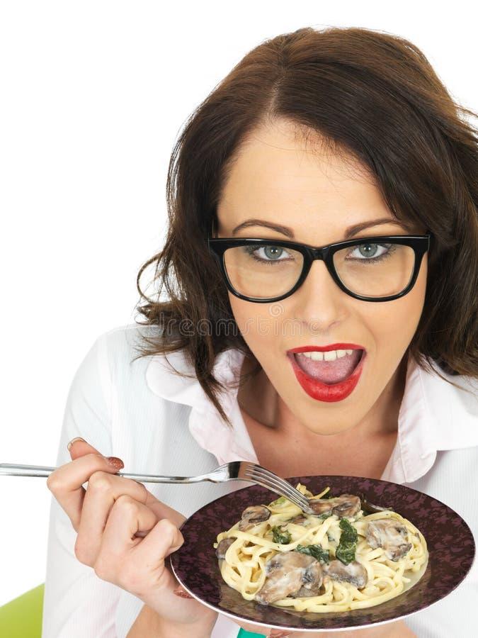 Mulher latino-americano nova feliz bonita que guarda uma placa do Linguine do vegetariano com espinafres e cogumelos fotos de stock royalty free