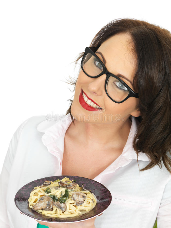 Mulher latino-americano nova feliz bonita que guarda uma placa do Linguine do vegetariano com espinafres e cogumelos imagens de stock