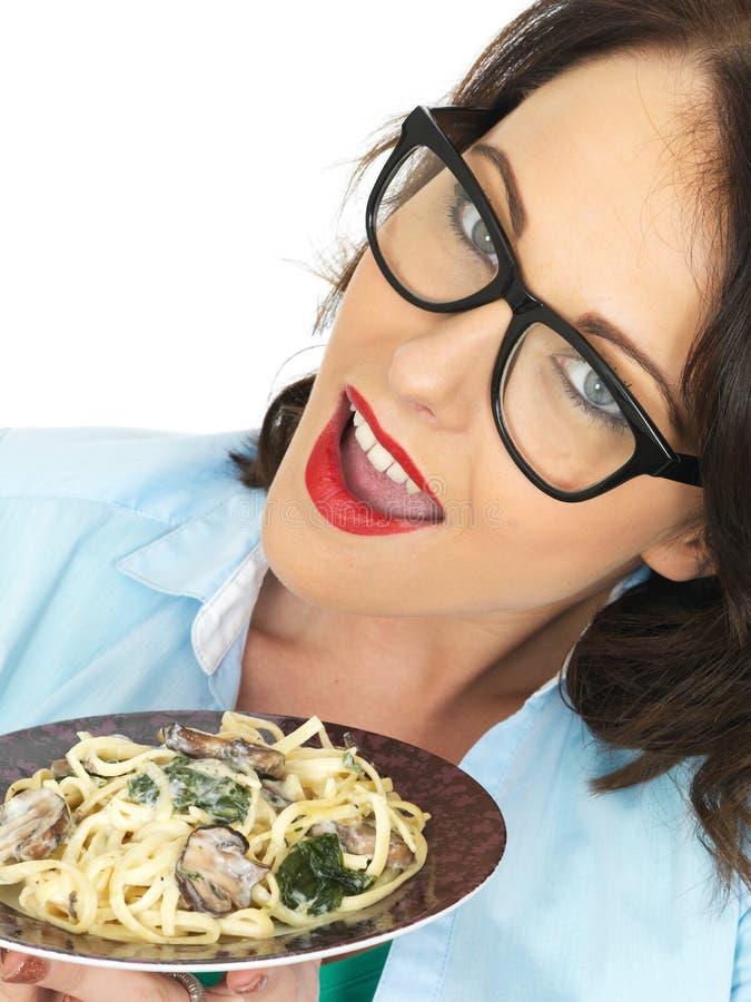 Mulher latino-americano nova feliz bonita que guarda uma placa do Linguine do vegetariano com espinafres e cogumelos foto de stock