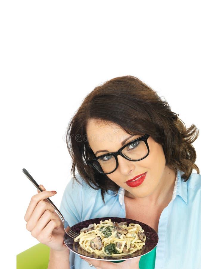 Mulher latino-americano nova feliz bonita que guarda uma placa do Linguine do vegetariano com espinafres e cogumelos fotos de stock