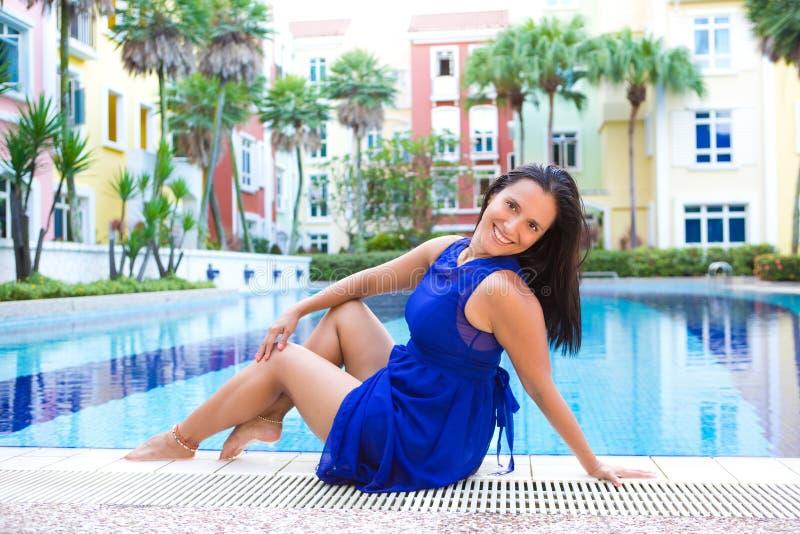 Mulher latino-americano nova no vestido azul que relaxa pela piscina fotografia de stock royalty free