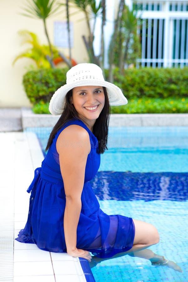 Mulher latino-americano nova no vestido azul que relaxa pela piscina imagens de stock