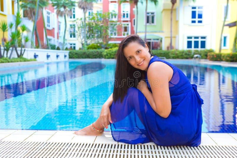 Mulher latino-americano nova no vestido azul que relaxa pela piscina cercada por flores imagem de stock royalty free