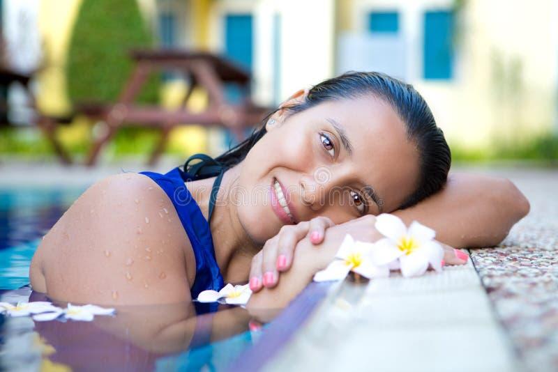 Mulher latino-americano nova no vestido azul que relaxa pela piscina cercada por flores fotos de stock