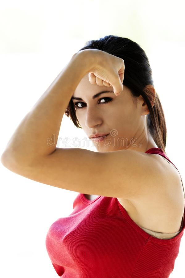 Mulher latino-americano nova que mostra fora o bíceps na parte superior vermelha imagens de stock royalty free