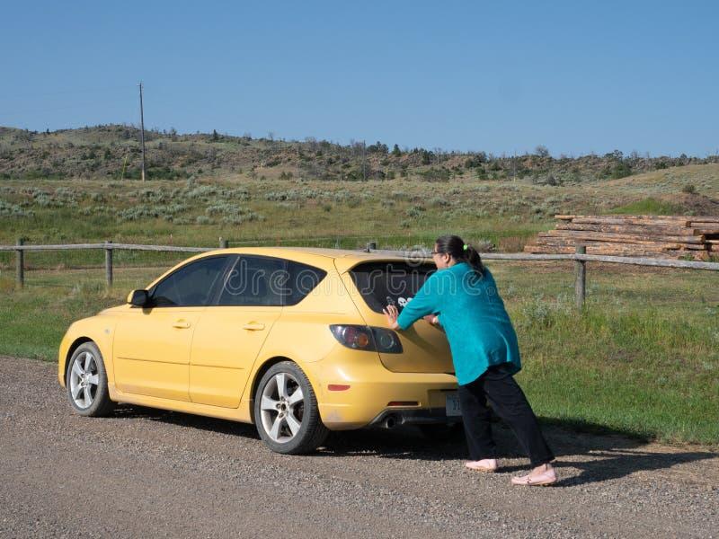 Mulher latino-americano que empurra um carro amarelo fotografia de stock