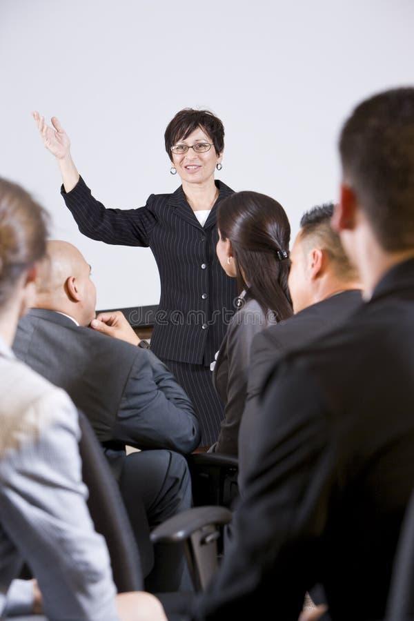Mulher latino-americano que fala ao grupo de empresários imagens de stock