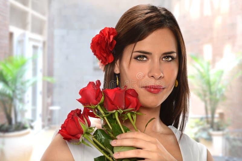 Mulher latino-americano que guardara rosas vermelhas foto de stock