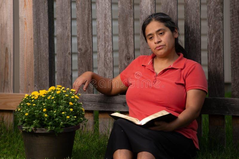 Mulher latino-americano que medita sobre sua leitura da Bíblia pelo potenciômetro de flor imagens de stock