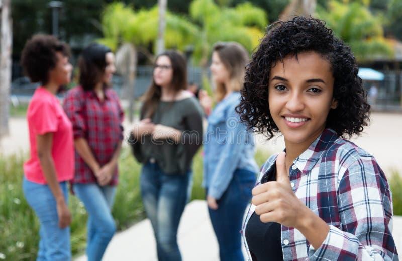 Mulher latino-americano que mostra o polegar com grupo de amigas imagens de stock royalty free