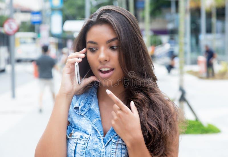 Mulher latino-americano surpreendida no revestimento das calças de brim no telefone fotos de stock