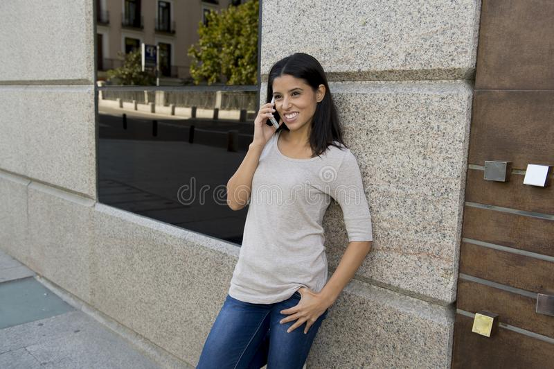 Mulher latino bonita e atrativa feliz nova que fala no telefone celular na rua na cidade fotografia de stock