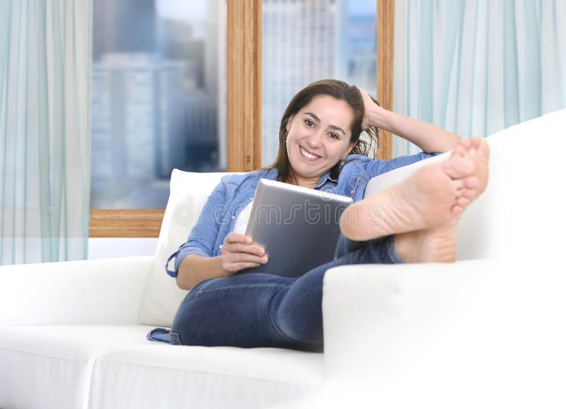 Mulher latino bonita que senta-se no sofá do sofá da sala de visitas em casa que aprecia usando o tablet pc digital fotos de stock