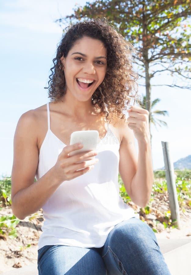 Mulher latino que recebe a boa notícia no telefone imagem de stock royalty free