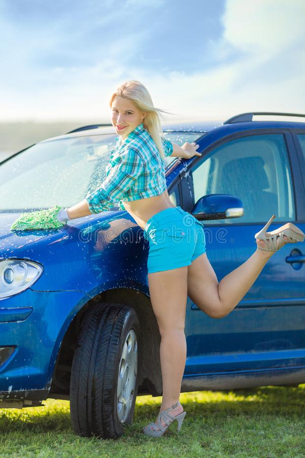 A mulher lava o carro imagens de stock royalty free