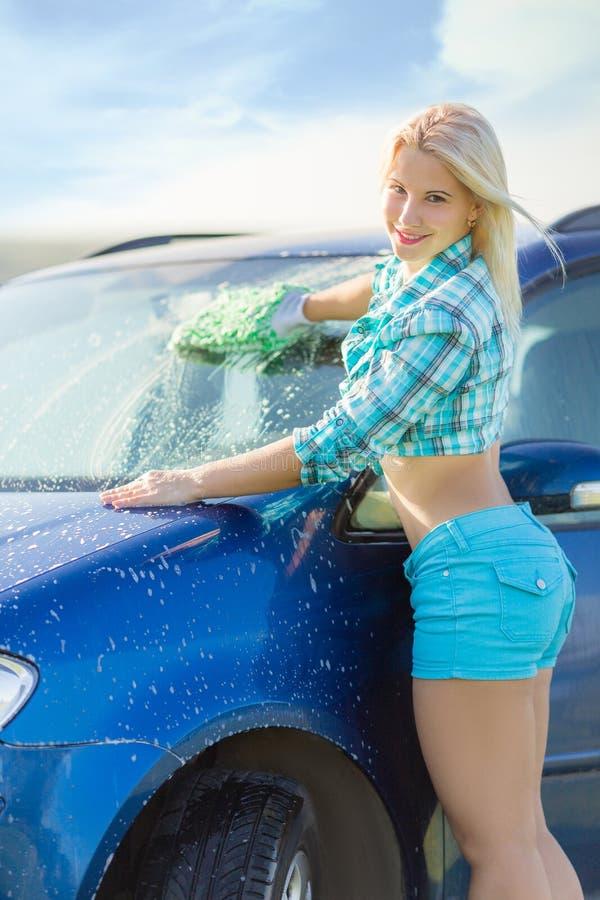 A mulher lava o carro imagem de stock