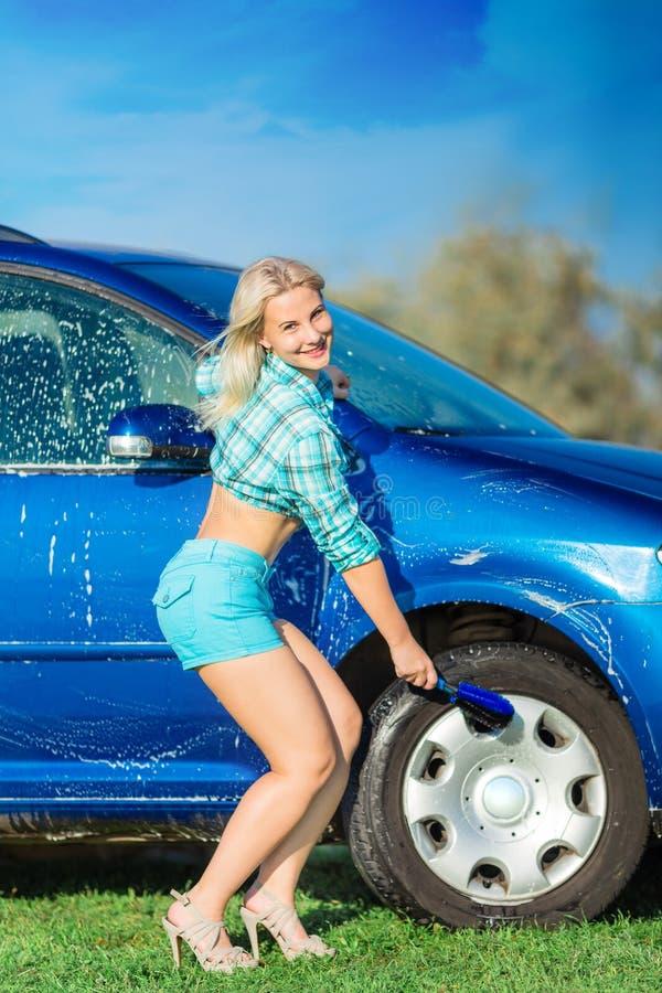 A mulher lava o carro fotos de stock
