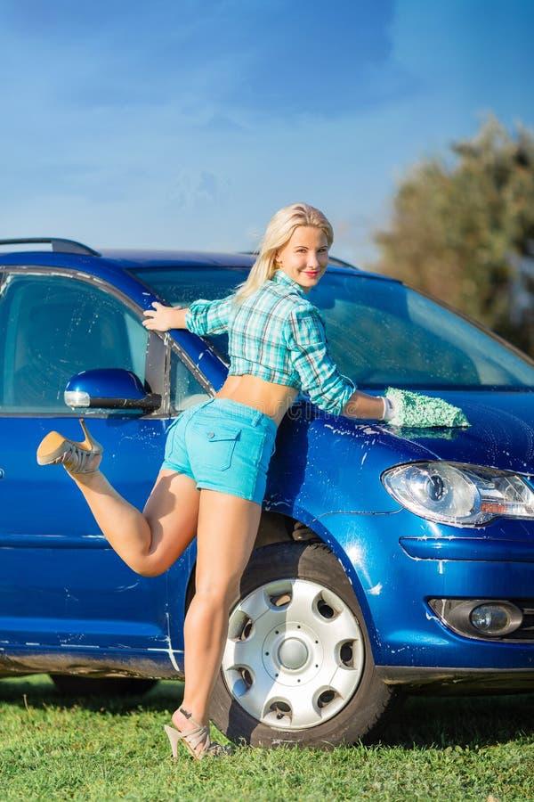 A mulher lava o carro foto de stock royalty free