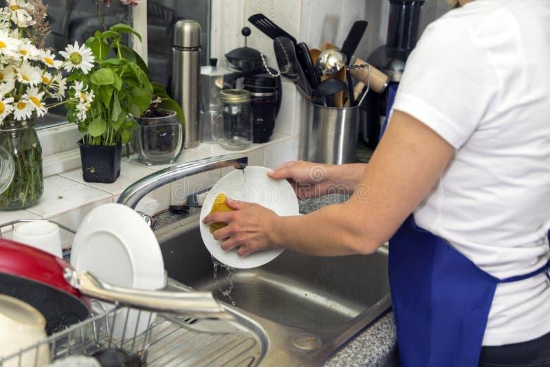 A mulher lava pratos na cozinha fotografia de stock
