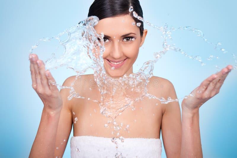 A mulher lava sua face com água fotos de stock royalty free
