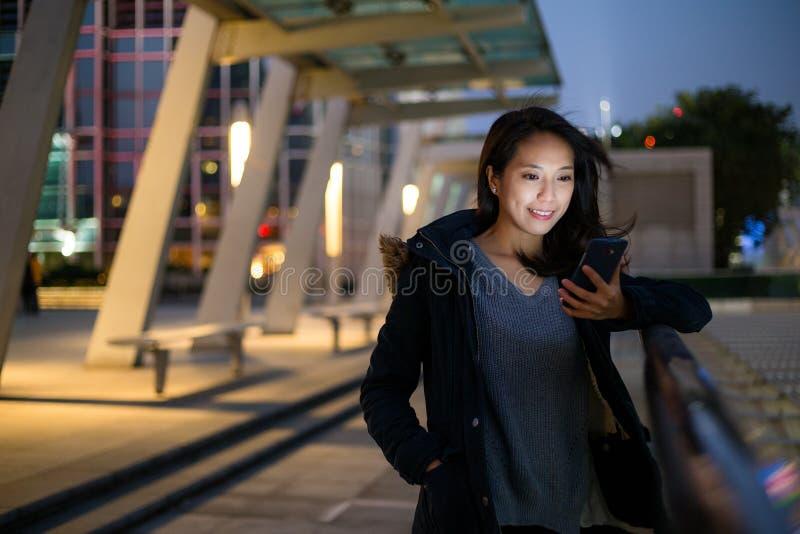 A mulher leu na mensagem de texto no telefone na noite foto de stock royalty free