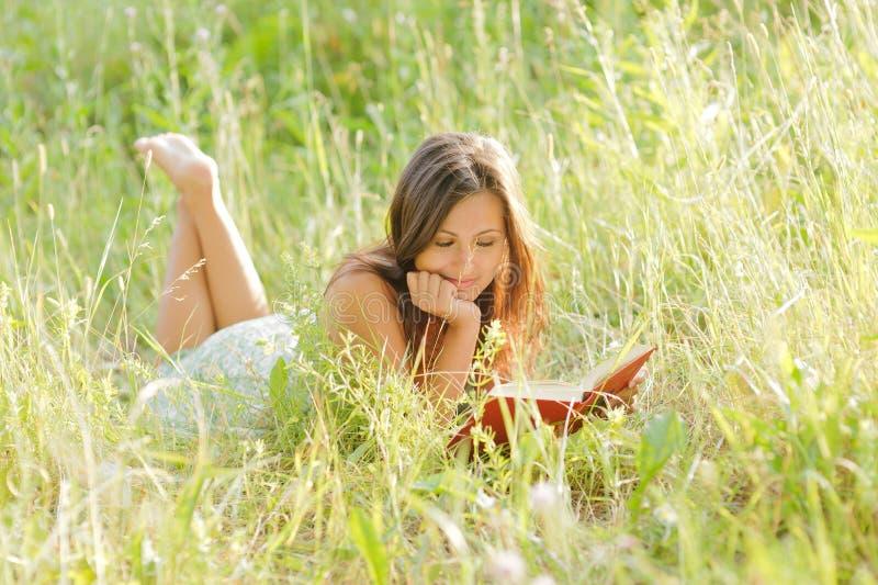 A mulher leu o livro no parque imagens de stock